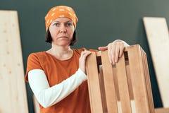 Carpintero de sexo femenino orgulloso que presenta con el cajón de madera acabado fotografía de archivo