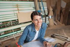 Carpintero de sexo femenino pensativo Working On Blueprint imagenes de archivo