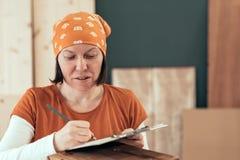 Carpintero de sexo femenino que escribe notas del proyecto de DIY imagen de archivo libre de regalías