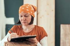 Carpintero de sexo femenino que escribe notas del proyecto de DIY fotos de archivo libres de regalías