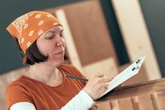 Carpintero de sexo femenino que escribe notas del proyecto de DIY fotografía de archivo