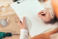 Carpintero de sexo femenino que escribe notas del proyecto de DIY imágenes de archivo libres de regalías