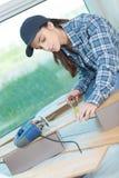 Carpintero de sexo femenino que mide al tablero de madera conveniente en taller imagenes de archivo