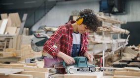 Carpintero de sexo femenino que trabaja con madera usando la máquina pulidora eléctrica en taller almacen de video