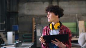 Carpintero de sexo femenino serio que trabaja con la tableta en pantalla táctil que camina del taller metrajes
