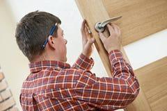 Carpintero de sexo masculino en la instalación de la cerradura imágenes de archivo libres de regalías