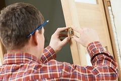 Carpintero de sexo masculino en la instalación de la cerradura foto de archivo