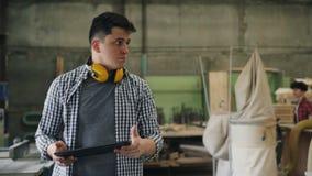 Carpintero de sexo masculino que camina en la pantalla de madera de la tableta del taller y de tacto metrajes