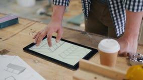 Carpintero de sexo masculino que mira dibujos técnicos de los muebles en la pantalla de la tableta almacen de metraje de vídeo