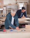 Carpintero de sexo masculino Working On Blueprint en el taller fotos de archivo