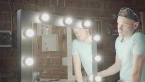 Carpintero del retrato que comprueba el espejo con las luces si su trabajo o no trabajo Fabricaci?n de la mano Craftman trabaja e almacen de metraje de vídeo