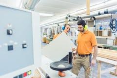 Carpintero en la fábrica de los muebles que examina el pedazo en el QA fotos de archivo