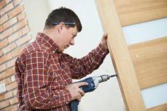 Carpintero en la instalación de la cerradura de puerta foto de archivo