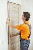 Carpintero en la instalación de la puerta fotos de archivo