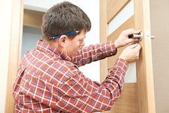 Carpintero en la instalación de la cerradura de puerta Foto de archivo libre de regalías