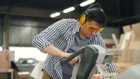Carpintero en las gafas y los auriculares que trabajan con la sierra eléctrica en taller almacen de metraje de vídeo