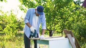 Carpintero en los vidrios protectores que cortan el tablón de madera con el rompecabezas eléctrico metrajes