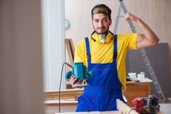 Carpintero joven del reparador que trabaja con poli eléctrico de las herramientas eléctricas Fotografía de archivo