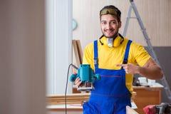 Carpintero joven del reparador que trabaja con poli eléctrico de las herramientas eléctricas Imágenes de archivo libres de regalías