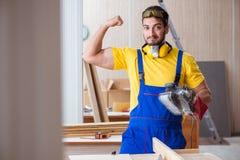 Carpintero joven del reparador que trabaja con poli eléctrico de las herramientas eléctricas Fotografía de archivo libre de regalías