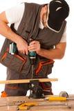 Carpintero joven que perfora un agujero en un listón de madera aislado sobre w foto de archivo