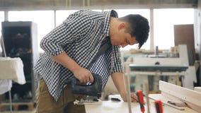 Carpintero joven que usa el instrumento del poder del rompecabezas a la madera de la sierra en taller almacen de video