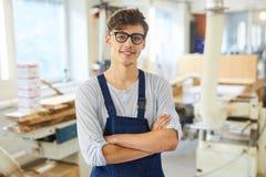 Carpintero joven sonriente en uniforme imagen de archivo libre de regalías