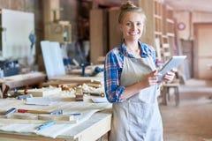 Carpintero joven Using Digital Tablet en tienda de las artesanías en madera imagen de archivo libre de regalías