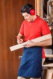Carpintero Marking On Wood con el lápiz Foto de archivo