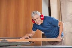 Carpintero mayor feliz Cutting Wood With Tablesaw fotos de archivo libres de regalías