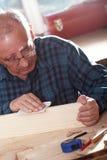 Carpintero mayor que envía el pedazo de madera con papel de lija Foto de archivo