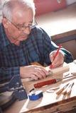Carpintero mayor que trabaja en hola taller Fotos de archivo libres de regalías
