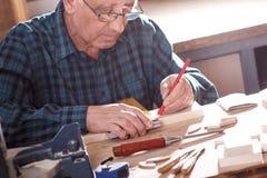 Carpintero mayor que trabaja en hola taller Imagen de archivo libre de regalías