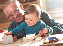 Carpintero mayor y su nieto que trabajan en el taller Imagen de archivo libre de regalías