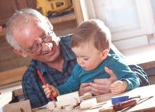 Carpintero mayor y su nieto que trabajan en el taller Fotos de archivo libres de regalías