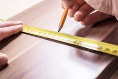 Carpintero Measuring un tablero de madera y fabricación Mark With de un lápiz imágenes de archivo libres de regalías
