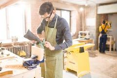Carpintero moderno en taller iluminado por el sol imagenes de archivo