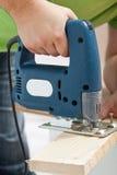 Carpintero o carpintero que trabaja con la sierra eléctrica Foto de archivo