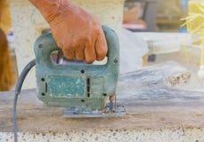 Carpintero o carpintero que trabaja con la sierra eléctrica - primer en las manos, carpintero en la naturaleza, carpintero en Tai Foto de archivo libre de regalías