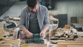 Carpintero ocupado con la correa que muele usando el instrumento del poder que trabaja en taller almacen de metraje de vídeo