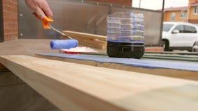 Carpintero Painting un tablero de madera de la terraza con la impermeabilización o la pintura del agua de la impregnación cierre  almacen de video