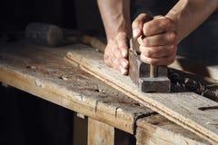 Carpintero que acepilla un tablón de la madera con un avión de la mano Imagenes de archivo