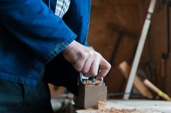 Carpintero que acepilla a un tablero de madera Fotografía de archivo libre de regalías