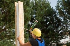 Carpintero que aplica el pegamento de madera a un panel Foto de archivo