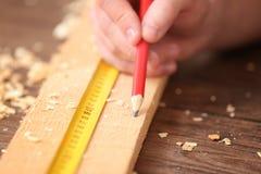 Carpintero que aplica la marca sobre el tablero de madera i imagenes de archivo