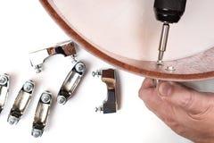 Carpintero que aprieta los tornillos en el cárter de tambor de madera del merbau Fotos de archivo libres de regalías