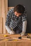 Carpintero que bosqueja el tablón de madera de pino para cortar en taller imagen de archivo