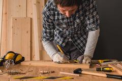 Carpintero que bosqueja el tablón de madera de pino para cortar en taller imagen de archivo libre de regalías