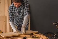 Carpintero que bosqueja el tablón de madera de pino para cortar en taller fotos de archivo