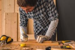 Carpintero que bosqueja el tablón de madera de pino para cortar en taller foto de archivo
